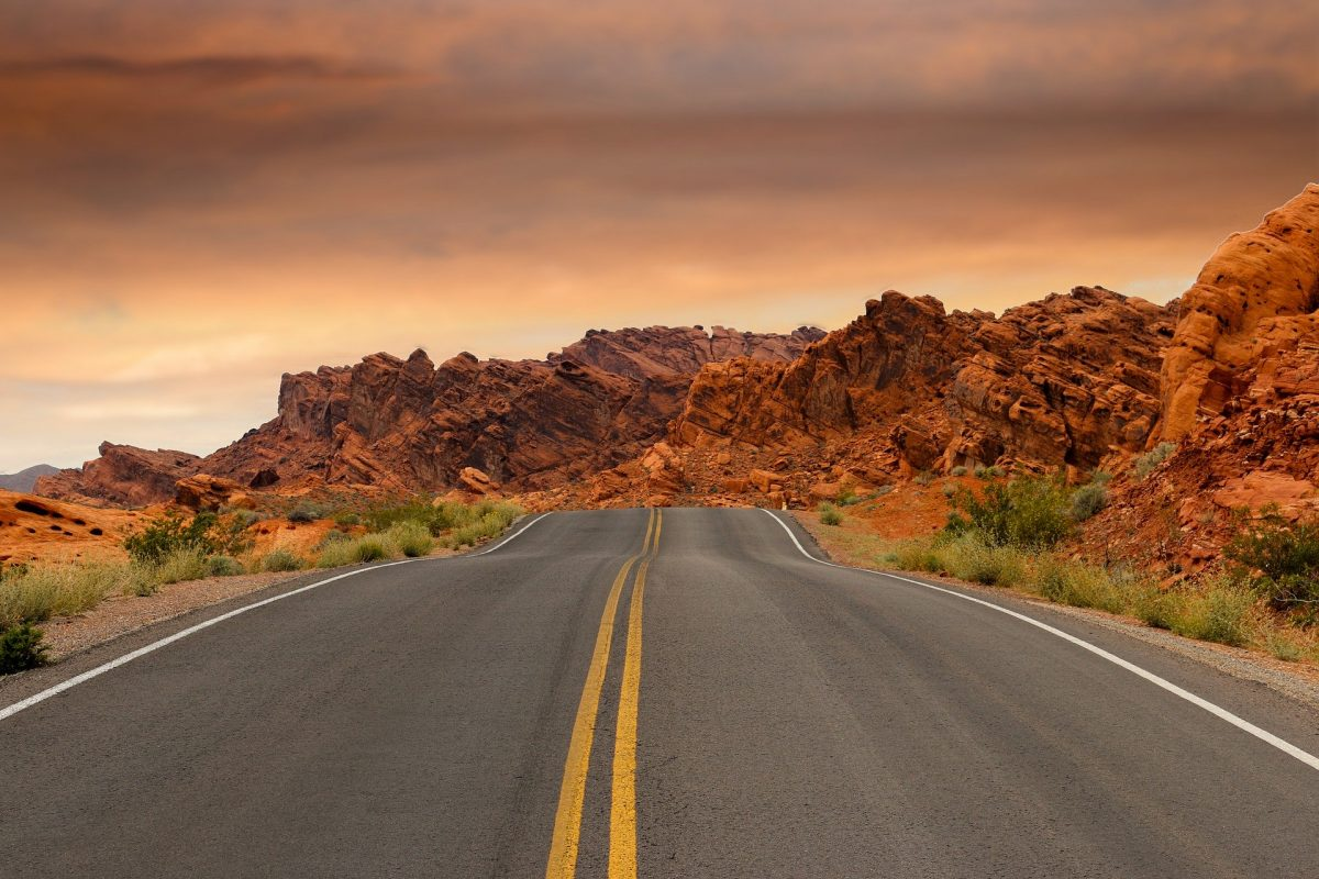 Two-lane road surrounded by red rocks in a dessert-like atmosphere