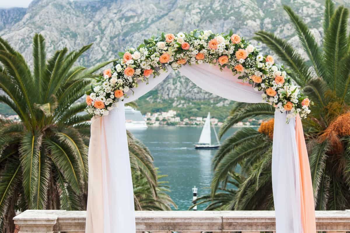 Knowing how to decorate a wedding arch with silk flowers can save you money while still giving you your dream wedding decor. Check out tips on how to do it!