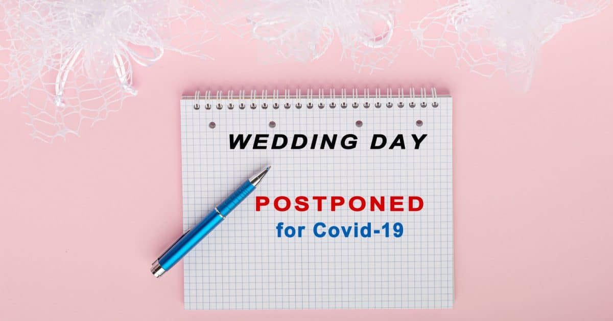Notebook with words Wedding day postponed for covid-19 /postponing a wedding has its bright sides