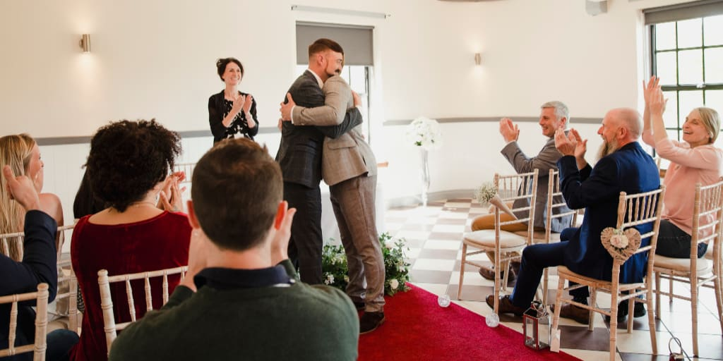 Two men are hugging after succesfully exchanging vows on their wedding day. All of their guests and the registrar are celebrating for them.