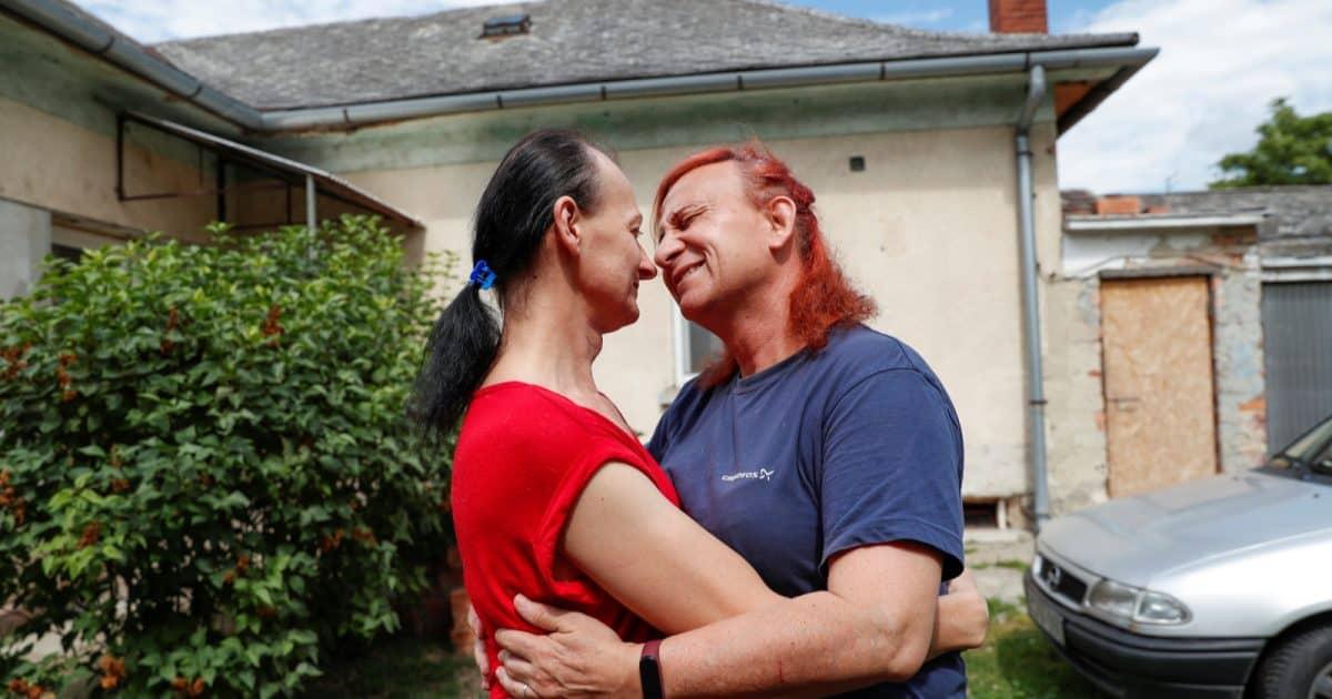 Hungarian transgender couple Tamara Csillag and Elvira Angyal embrace in their front yard.