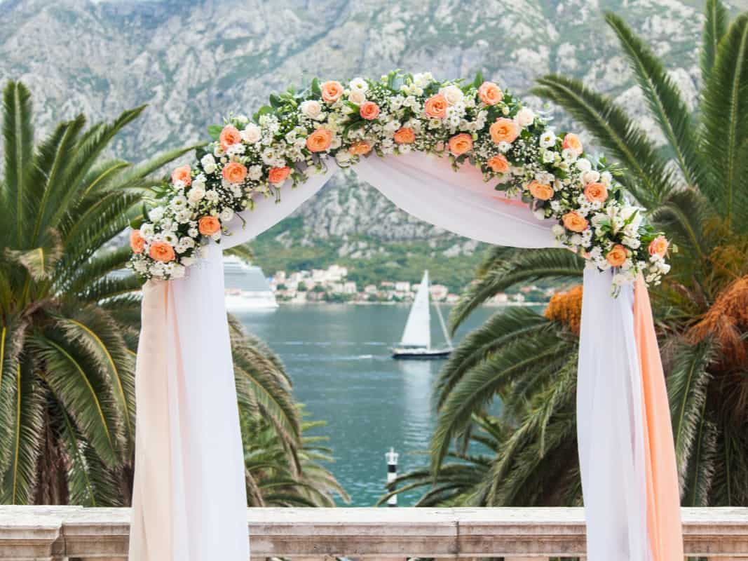 Wedding ceremony with flower arch near palm, sea, yacht, mountains. Flower decoration is from cream, orange, white roses.