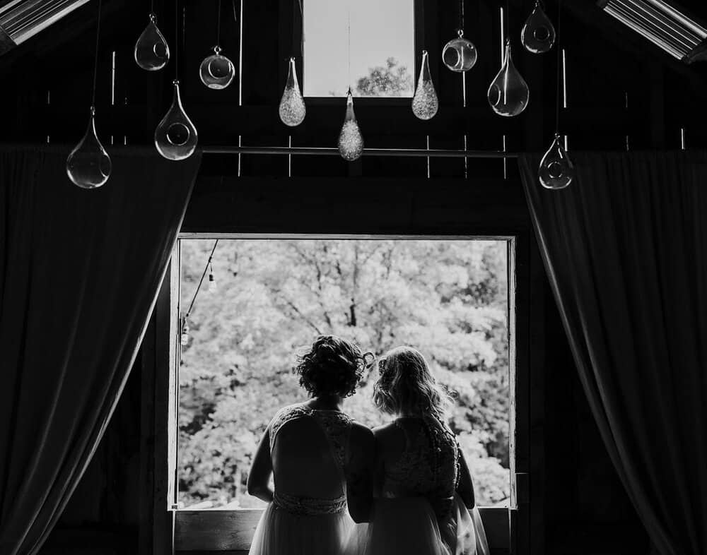 Lesbian wedding photos of Katrin and Christina, staring out the barn window.