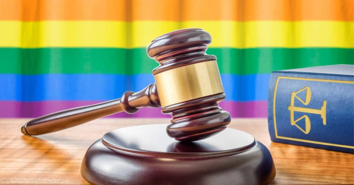 courtroom gavel against an LGBTQ flag background, depicting the struggle for same-sex marriage rights