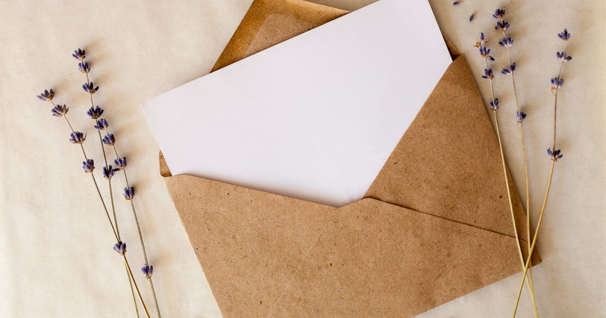 white invitation in a brown envelope