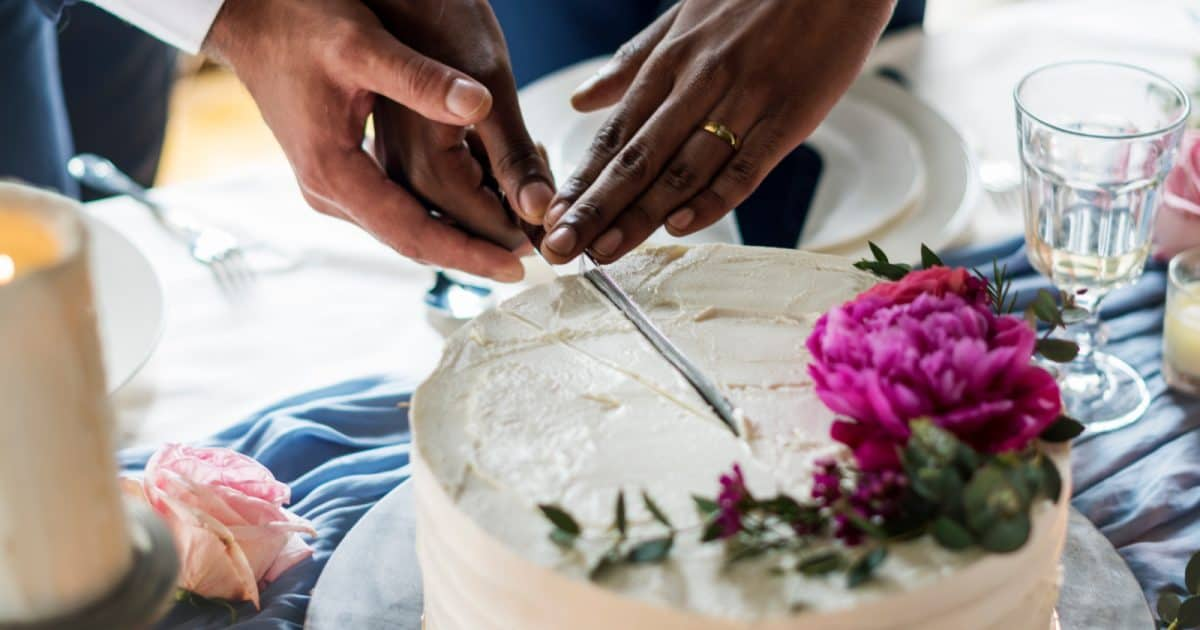 Two male hands cutting a wedding cake together after their gay wedding.
