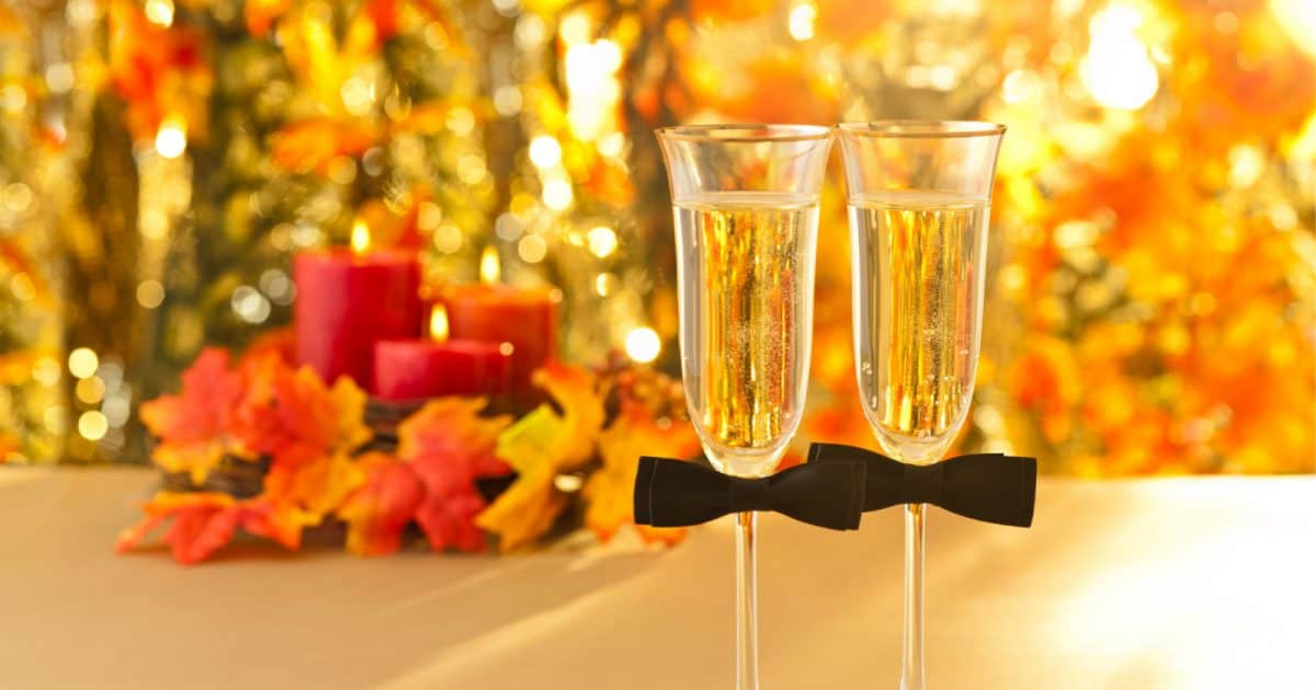 Champagne glasses for two grooms in front of a fall table setting, perfect for a rainbow-free same-sex wedding.