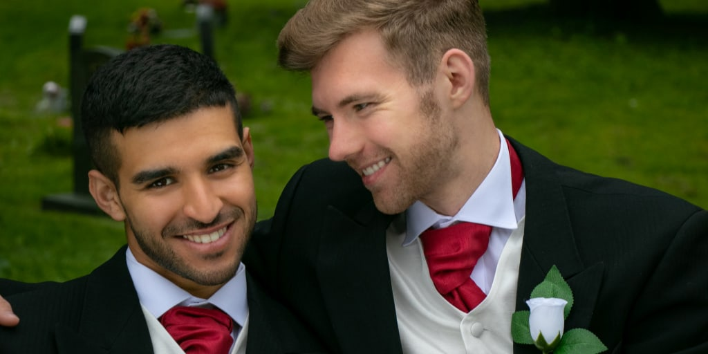 gay couple wearing a stunning suit and tie combo with a black jacket and a red tie