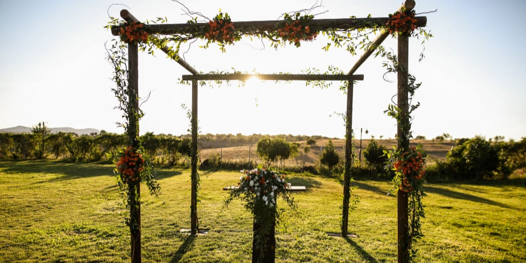 a wooden wedding arch with simple yet elegant flowers