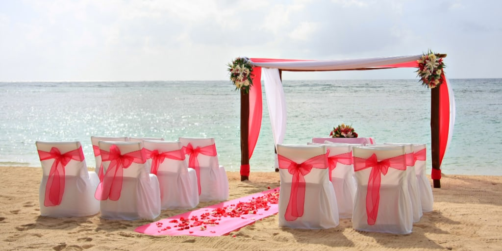 Gazebo and chairs set up for a romantic beach wedding, with red rose petals and a beautiful flower arch.