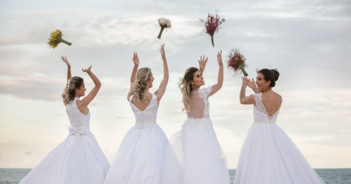 Cheerful same-sex wedding brides in beautiful gowns doing their bouquet toss