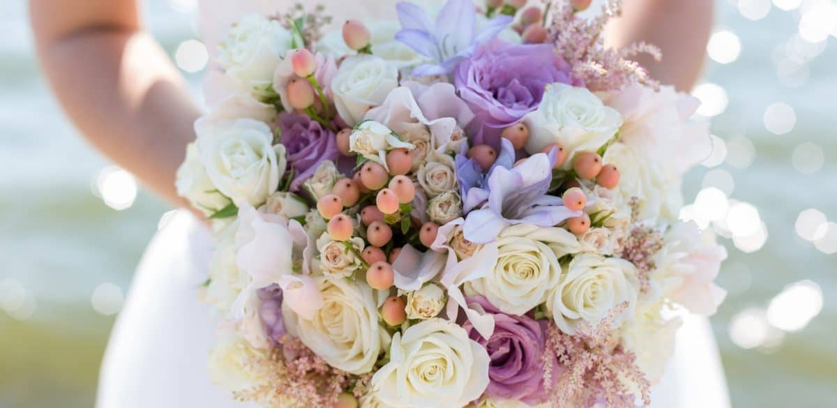 Bride holding a wedding bouquet filled with white and purple roses. Learn how to throw a cheap wedding for under $3K, flowers and all!
