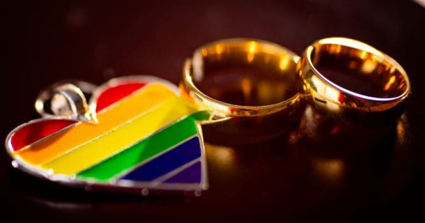 hers and hers wedding rings with lgbtq pride flag in a heart