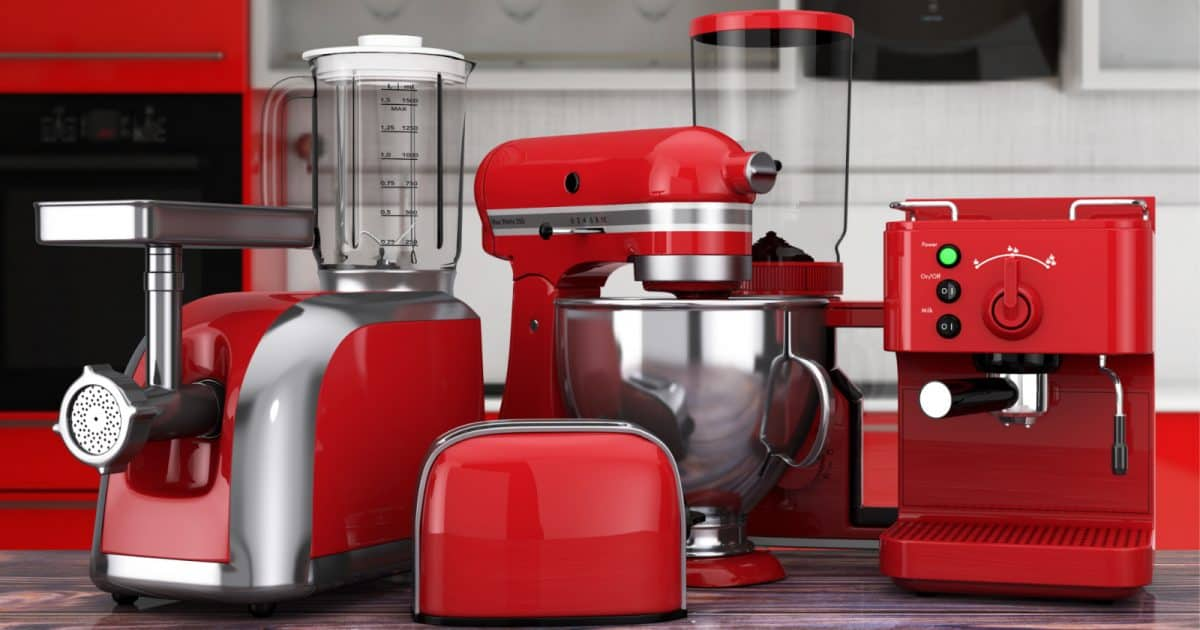 Shiny red kitchen wedding gifts, including a toaster, blender, and food processor