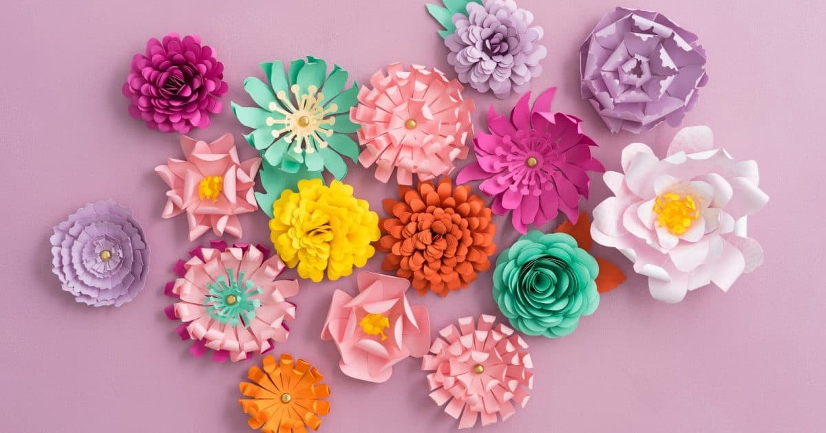 Colorful handmade paper flowers on pink background, perfect for a paper flower wedding arch
