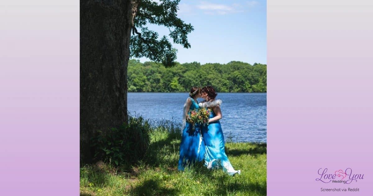 Two brides in blue dresses kissing after proving you really can have a classy socially distanced lesbian wedding