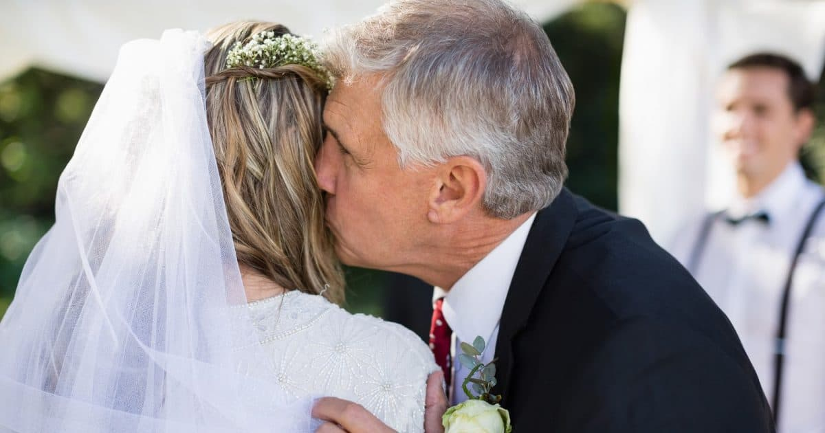 Affectionate father kissing his daughter during wedding