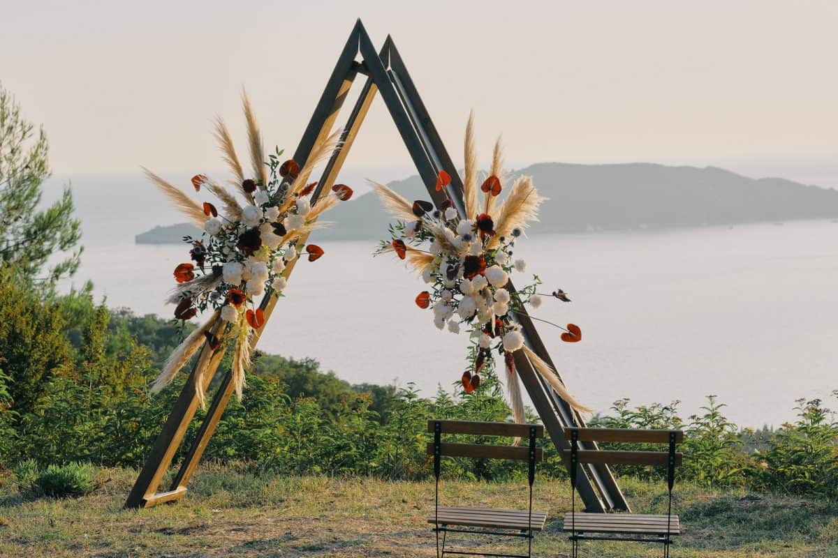 Original triangle wedding arch on top of the mountain with white and red flowers at sunset. Romantic ceremony in the style of boho