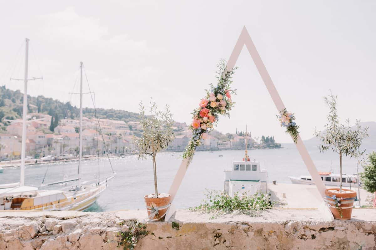 destination wedding triangle arch with sea view. Triangle wedding arch in Croatia. Destination wedding with unqiue flower arch.
