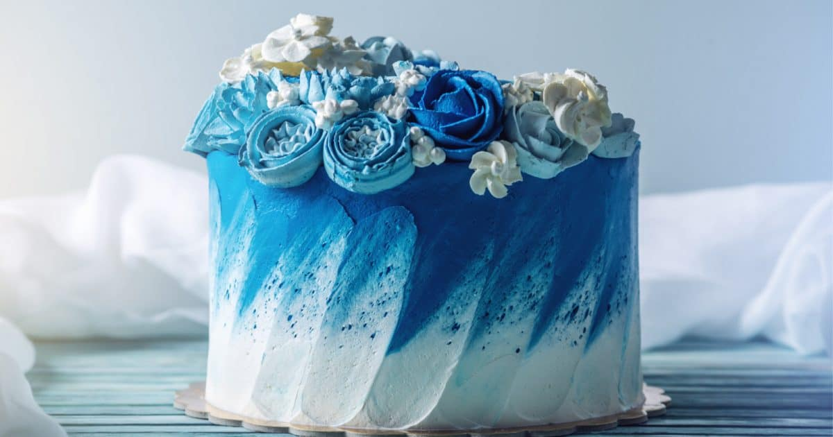 A blue and white cake topped with flowers, one of the most unique wedding cakes for a beach wedding