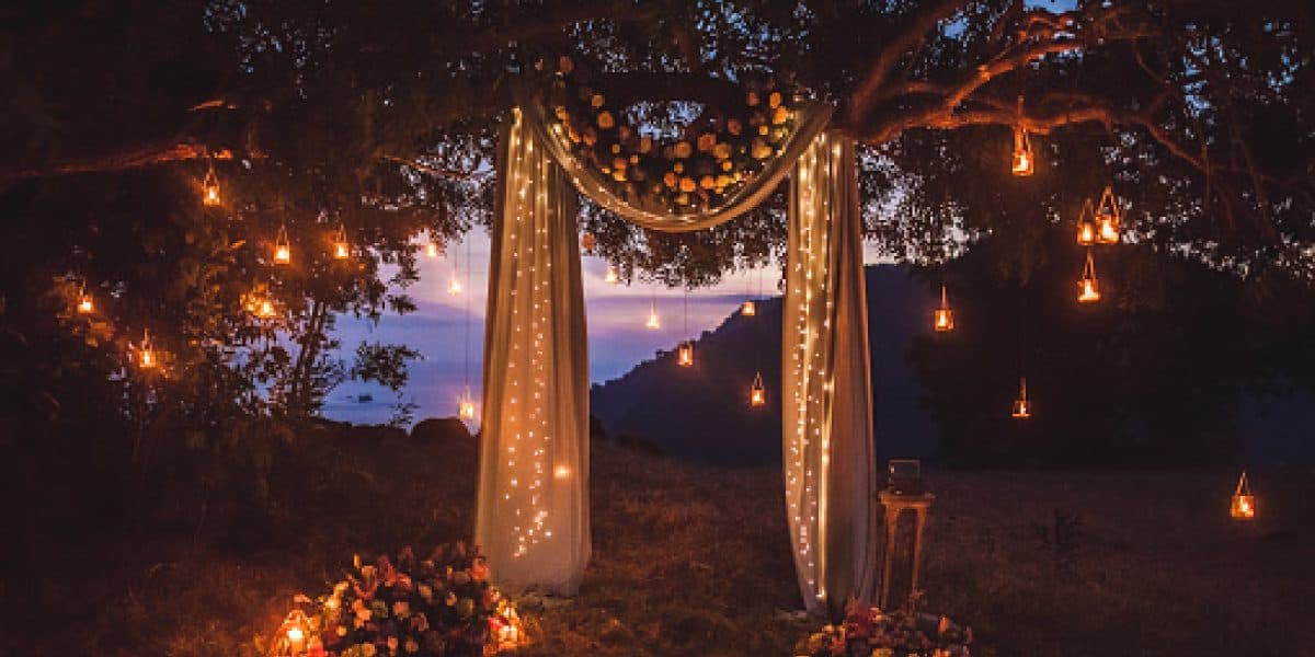 Night wedding ceremony with a lot of lights, candles, lanterns. Beautiful romantic shining decorations in twiligh