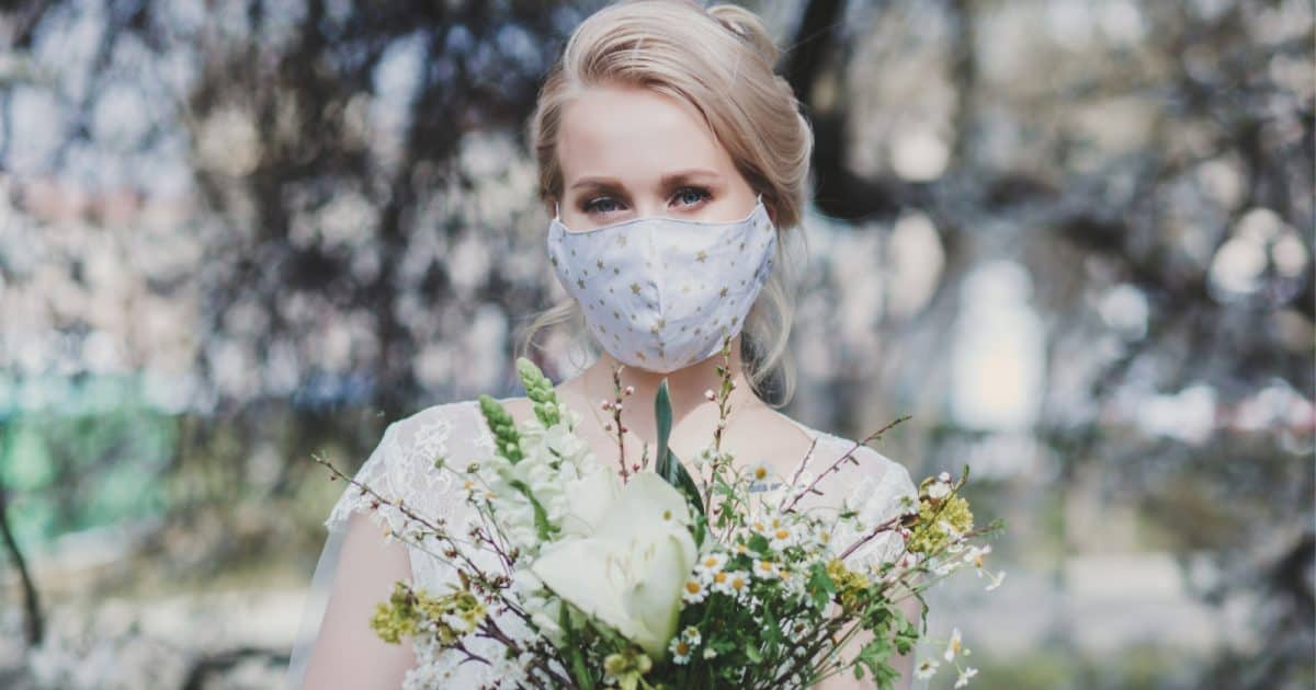 a bride wearing a wedding face mask and holding flowers