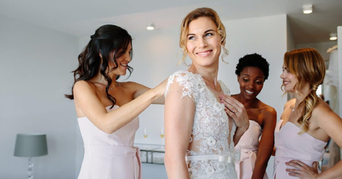 Bride and bridesmaids during the wedding preparations. Friends dressing the bride for wedding in a hotel room