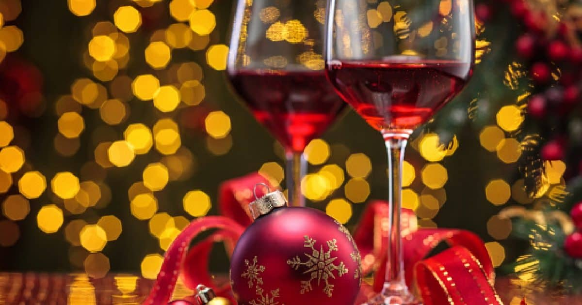 Red wine in wineglasses and Christmas ball against holiday lights background