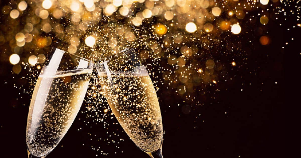 Two glasses of champagne toasting in the nigh with lights bokeh, glitter and sparks on the backgroun