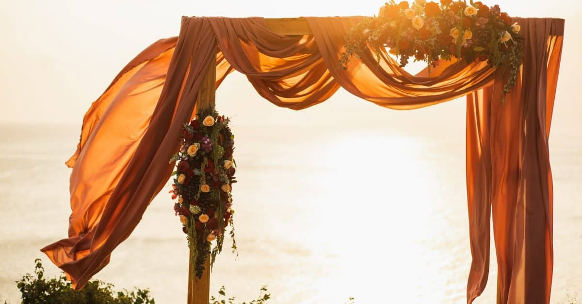 Square wooden wedding arch on outdoor sunset wedding ceremony. Red rose flowers and hanging cloth. Amazing warm sun light.