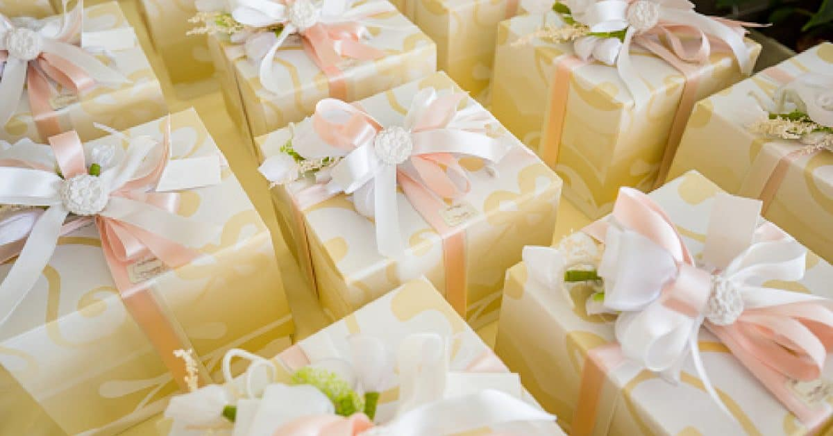 Wedding Gifts For Female Same-Sex Couples In Their 30s, wrapped up in gold swirled paper with pinks and white bows.