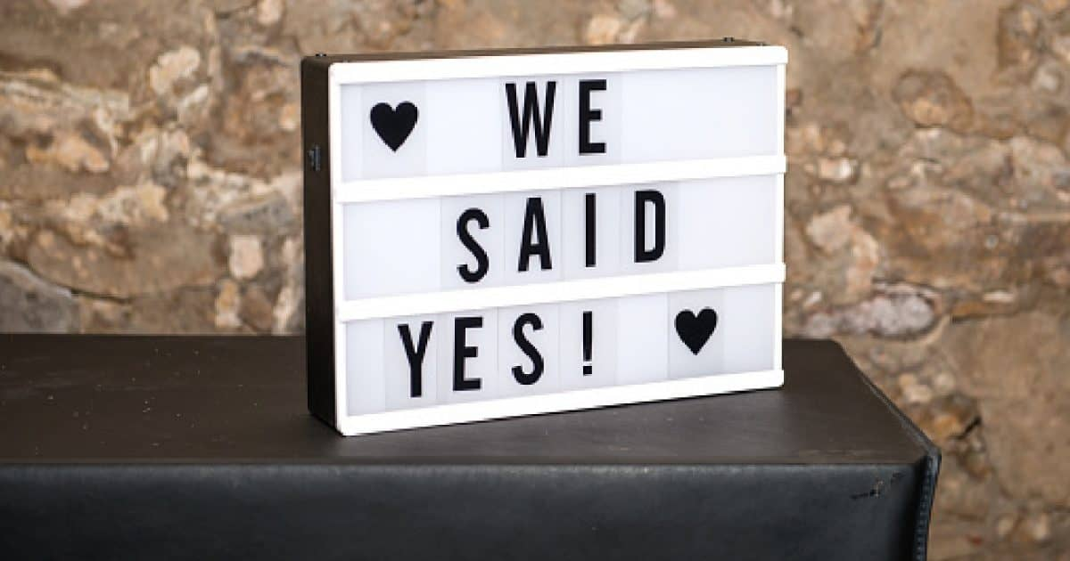 "Sign on a table that says ""We Said Yes,"" makes a great drive-by engagement party decoration!"