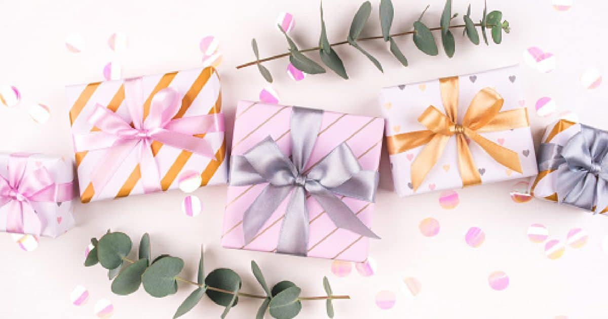 Set of gift boxes with bows, eucalyptus branches and confetti on a white background. Flat lay composition. Birthday, christmas, wedding or another holiday concept