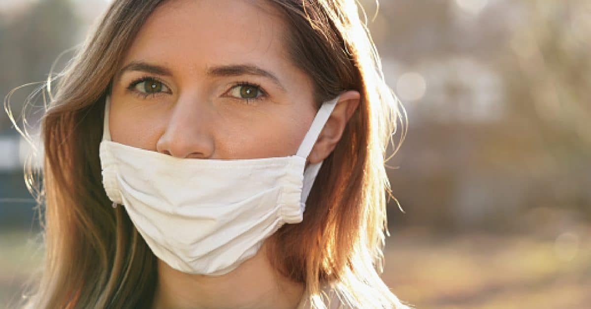 Young woman wears home made white cotton virus mouth face mask, wrong way, incorrect wearing - masks should cover nose as wel