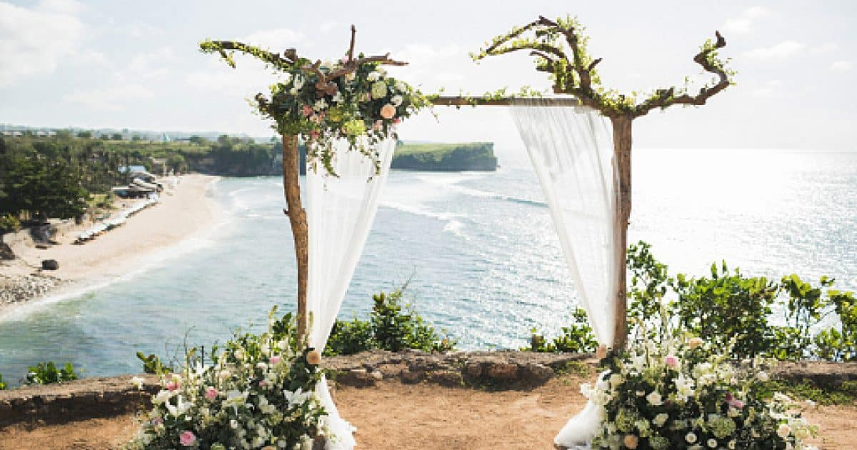 Sunset wedding ceremony arch with wooden branches and flower decoration and white cloth canopy. View of Balangan cliff in Bali. Wedding with ocean view