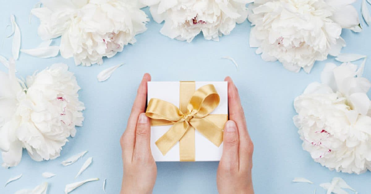 Womans hands giving gift or present box decorated white peony flowers on pastel table top view. Flat lay composition for birthday or wedding