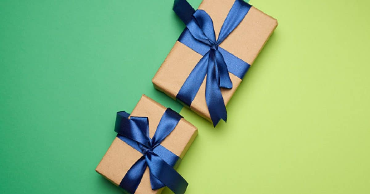 two rectangular boxes wrapped in brown paper and tied with a silk ribbon with a bow, gift on a green background, top vie