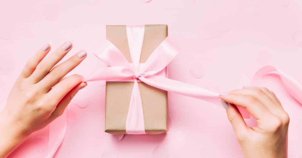 pink bow on a brown box with woman tying the bow