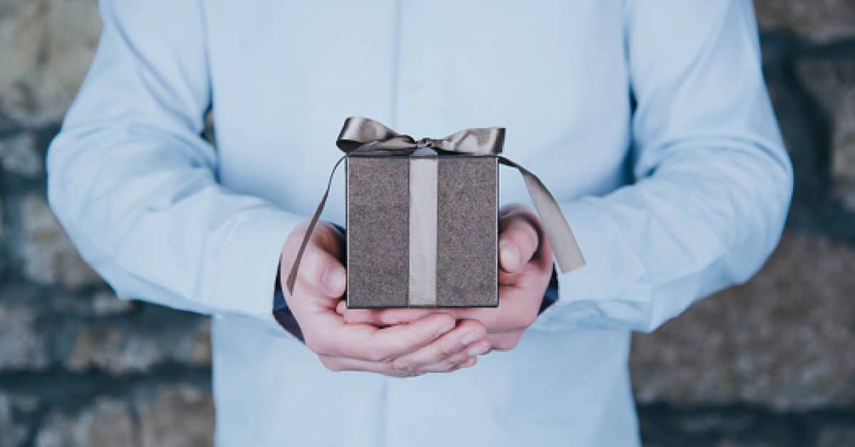 Male hands holding a gift against rustic background - engagement gifts for an older couple