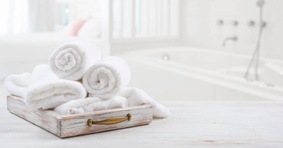 Vintage drawer with white towels over blurred bathroom and bedroo