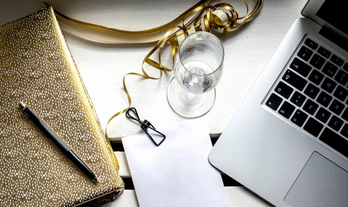 Luxury celebration preparations with golden notebook, empty champagne glass, laptop and binder clip on white envelope