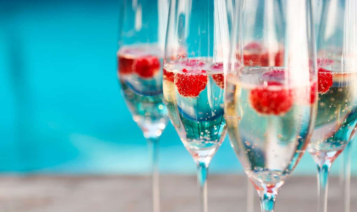 Champagne glasses with raspberry. Summer pool party