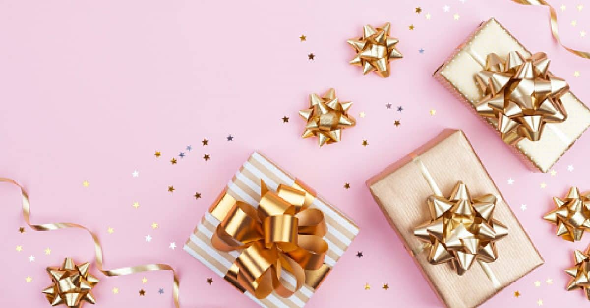 Fashion gifts or presents boxes with golden bows and star confetti on pink pastel background top view. Flat lay composition for birthday, christmas or wedding