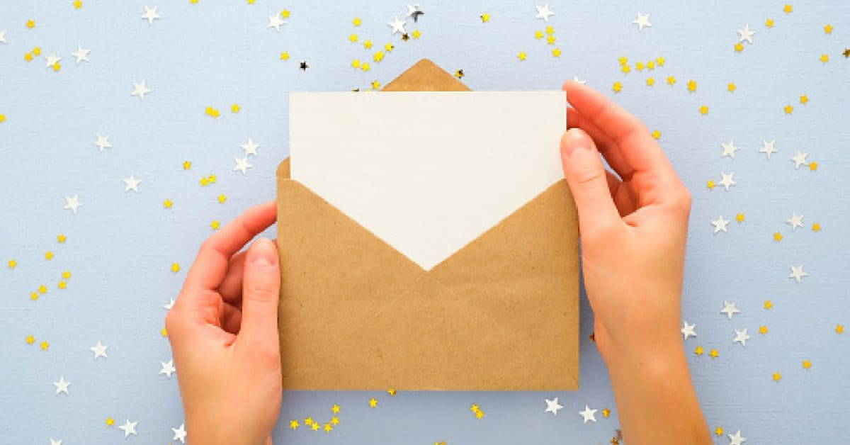 Female's hands holding kraft paper envelope letter with blank white card mockup over pastel blue background with golden confetti stars. Christmas, New Year, winter holidays and birthday concept