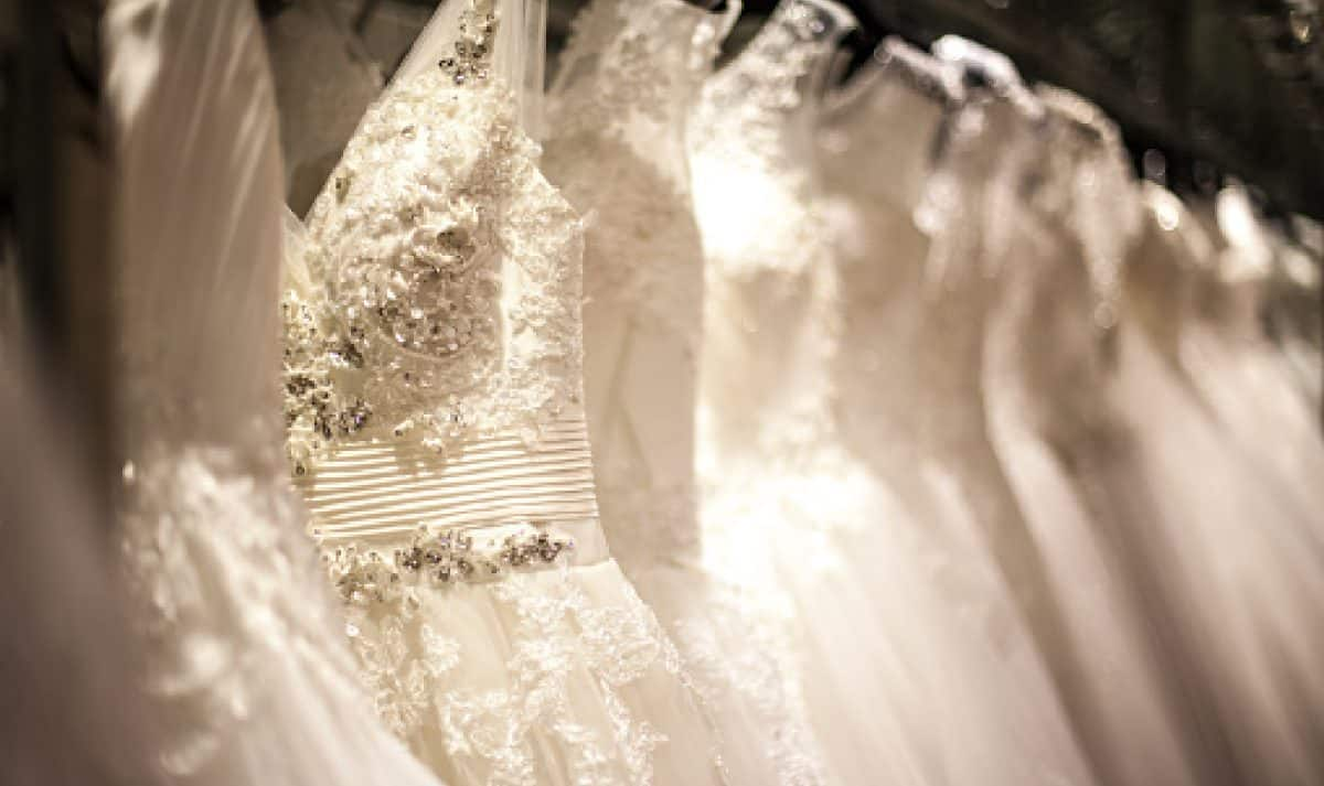 A shopping rack full of white minimony wedding dresses with different styles and sizes.