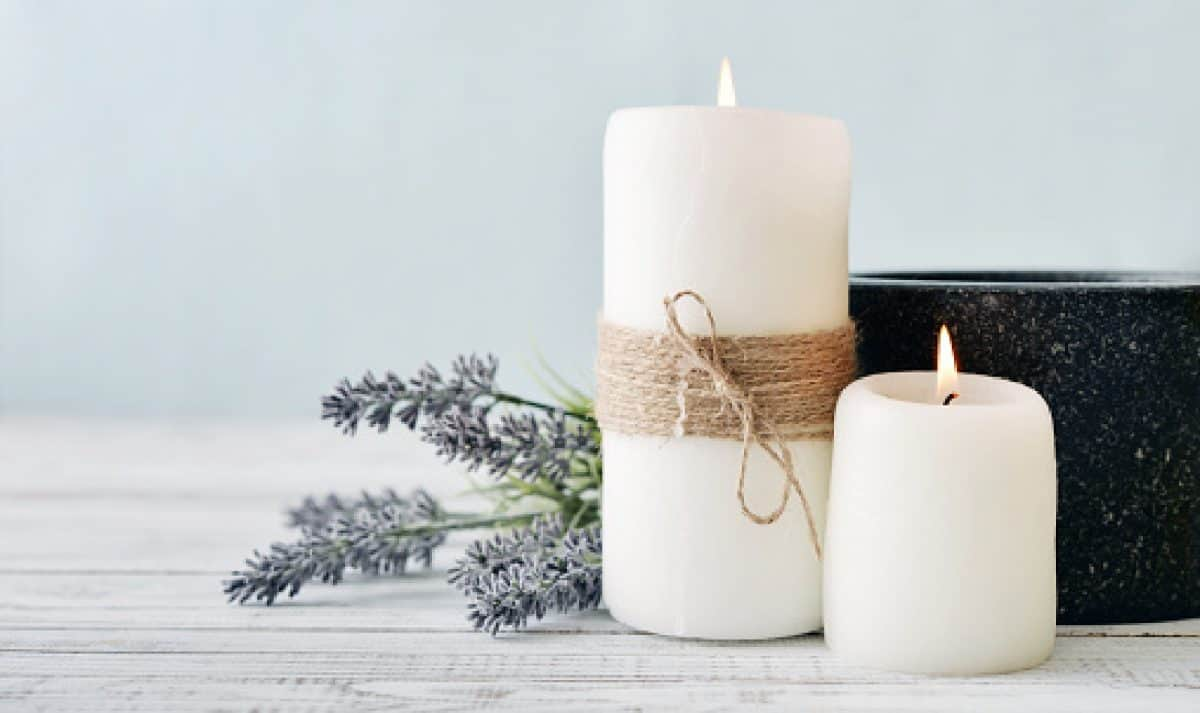 Two candles with lavender flowers on light blue background, candles make great lesbian wedding gifts under !