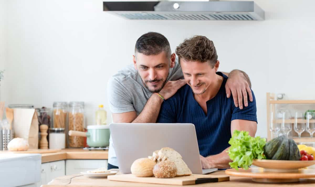 Happy gay male couple using internet having a good time together in kitchen at home