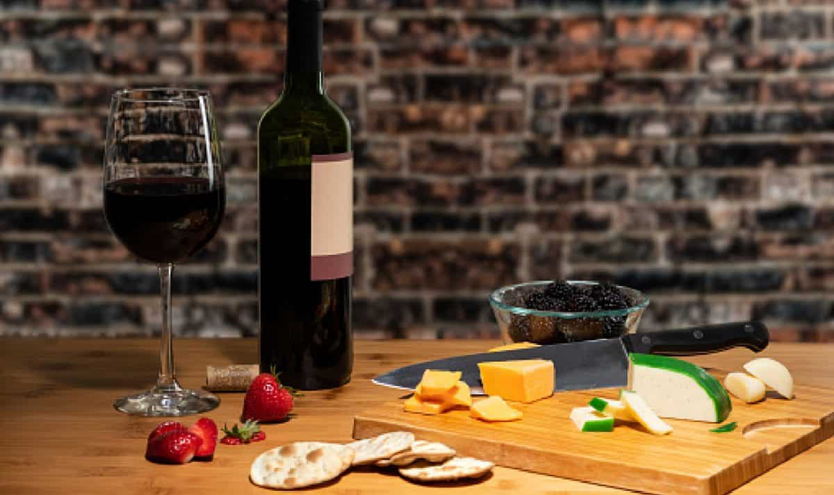 Wine and a glass accompanied by cheese on a table with a cutting board and cutlery with fruit