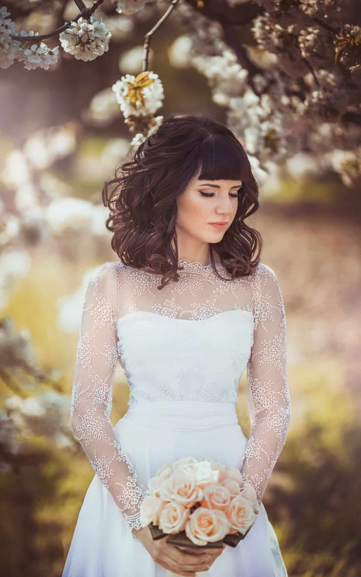 46504546 - beautiful bride with stylish make-up in white dress in spring garden