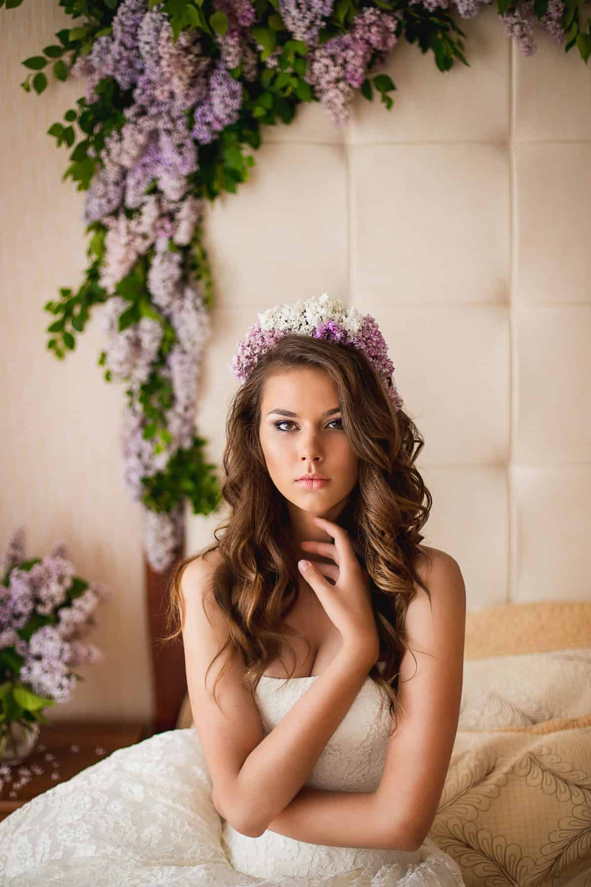 the bride in a wreath from a lilac lies on a bed, and nearby lilac flowers